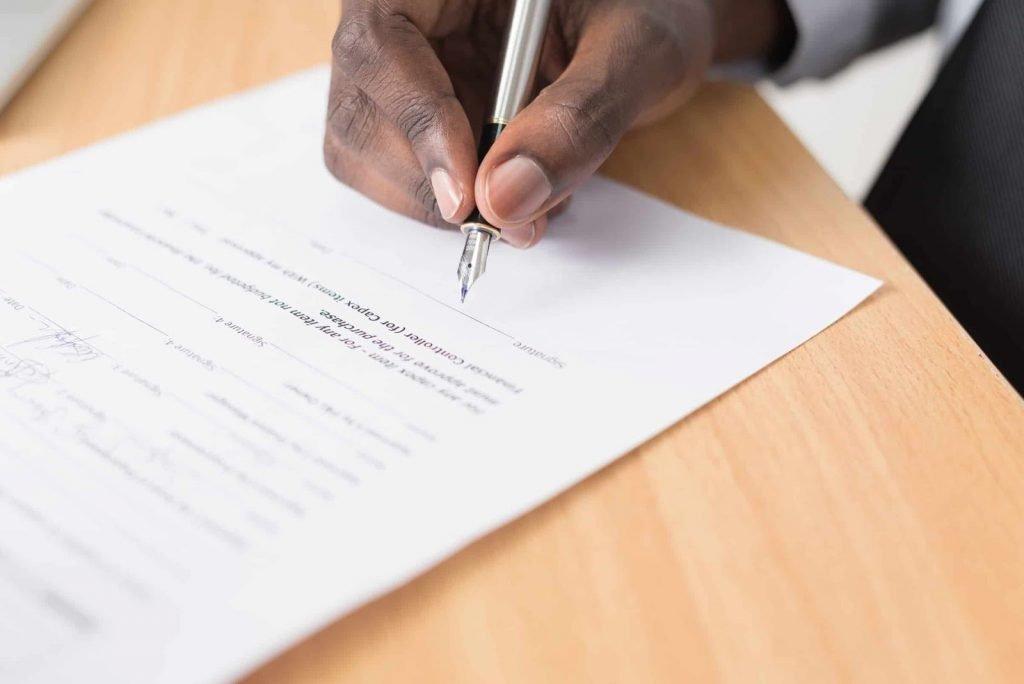 Zoom sur la main d'une personne signant le règlement intérieur du CSE