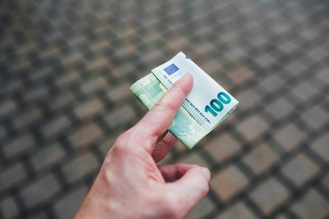 Main tenant un billet de 100 euro qui illustre le budget de fonctionnement du CSE