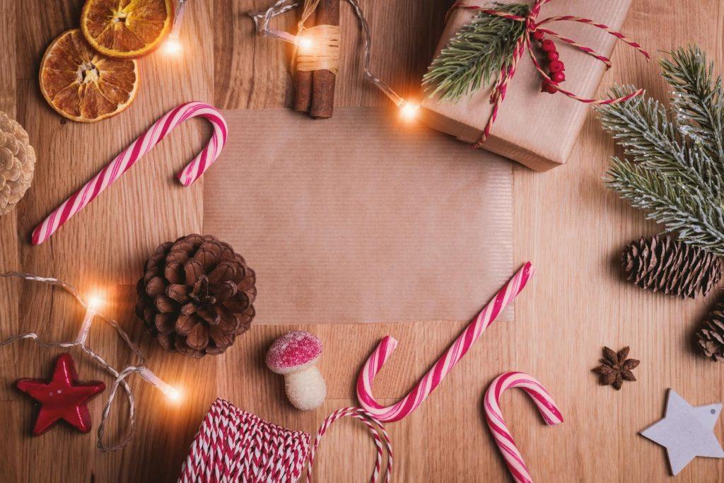 Table sur laquelle sont posés différents éléments représentant noël comme : des pommes de pins, des sucres d'orges et un cadeau